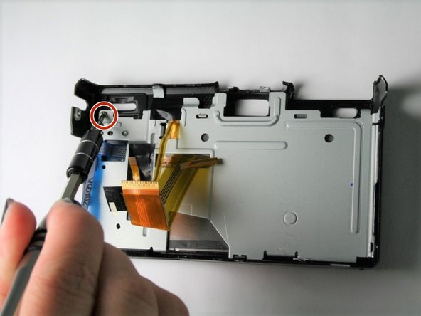 Using a Phillips #00 screwdriver, remove the 3.5 mm silver screw from the upper left hand corner of the back cover.