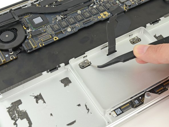 Use tweezers to remove the two trackpad mounting brackets from the upper case.