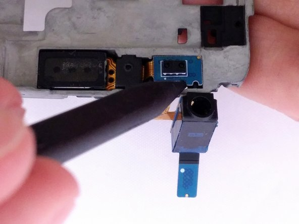 Image 2/3: Lift spudger away from support plate to remove headphone component.