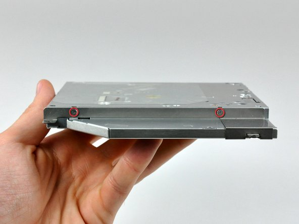 Image 1/2: Pull the optical drive bracket away from the thin side of the optical drive.