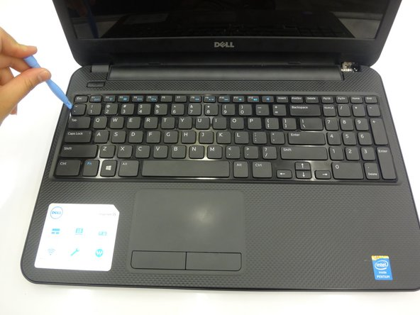 Using a flat head screwdriver, depress locking tabs holding keyboard into place