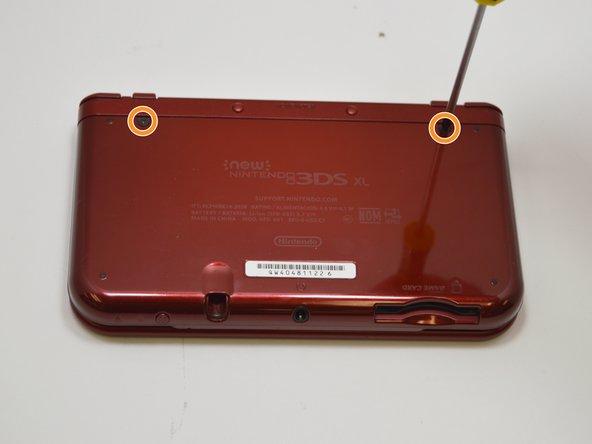 Gire el dispositivo de manera que la cubierta posterior quede hacia usted y ubique los dos tornillos en la parte superior.