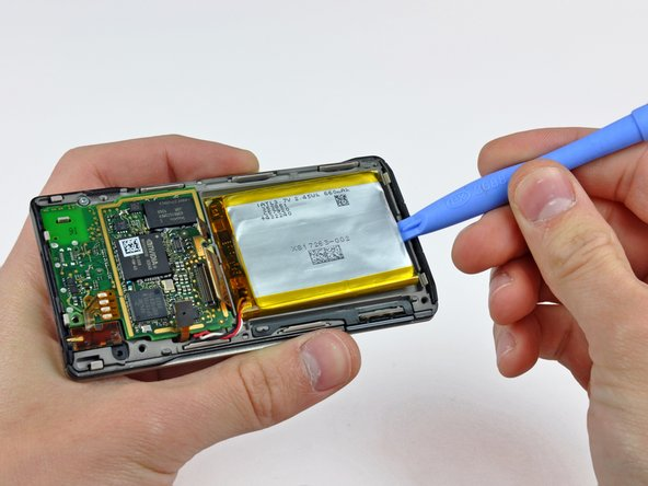 Use a Zune opening tool to carefully pry the battery off the adhesive securing it to the inner chassis.