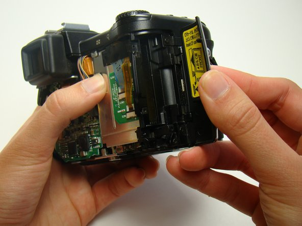 Image 1/2: Remove the Phillips screw near the top of the camera.