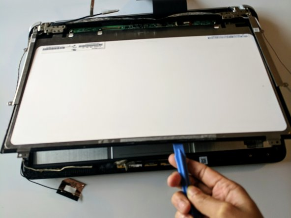 Using a plastic prying tool, remove the display panel.