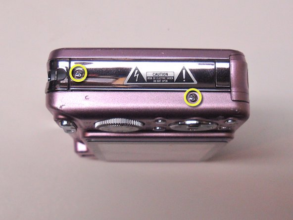 Image 2/3: Remove the two identical small Phillips screws on the right side of the camera.