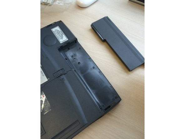 Image 1/1: Slide entire battery pack toward the edge of the laptop in order to unlock it.