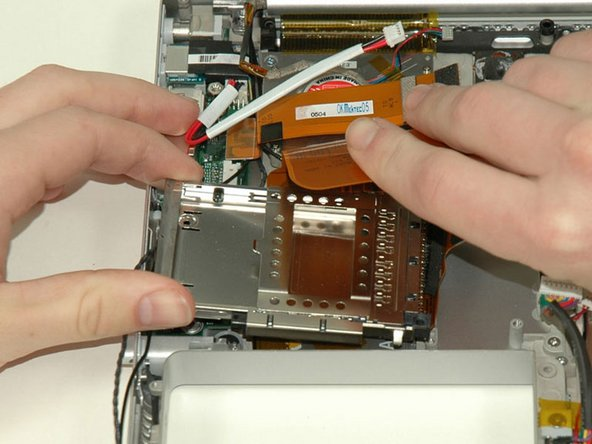 Image 1/1: When replacing the PC card cage, make sure you attach it to the post on the metal eject button.