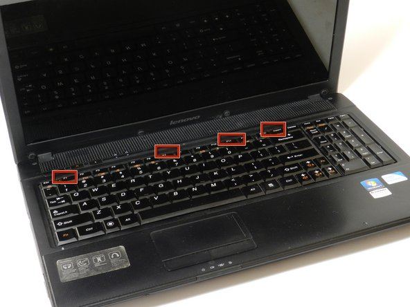 Image 1/1: Using the plastic opening tool, push in the four small, plastic tabs located at the top of the keyboard.