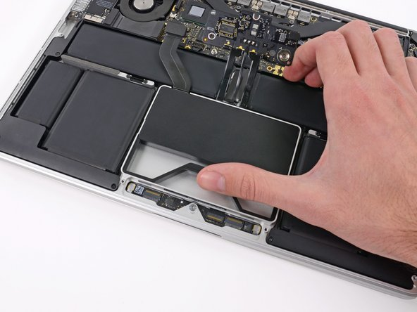Use your thumb or finger to bend the plastic spring bar on the SSD tray, freeing the two clips at the front side of the device.