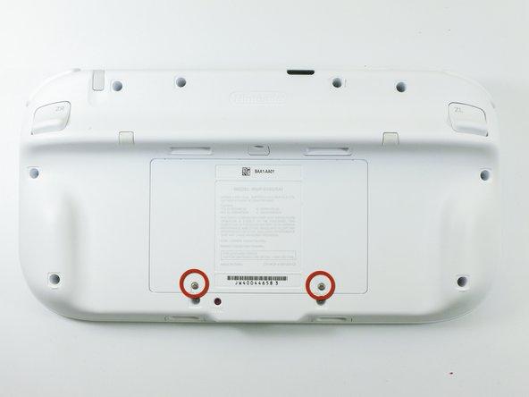 Le GamePad tourné vers le bas, dévissez les deux vis cruciformes Phillips #00 fixées au cache de la batterie.