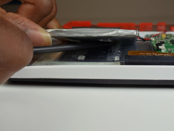 Use your spudger to separate the battery from the adhesive glue strips and plastic film.