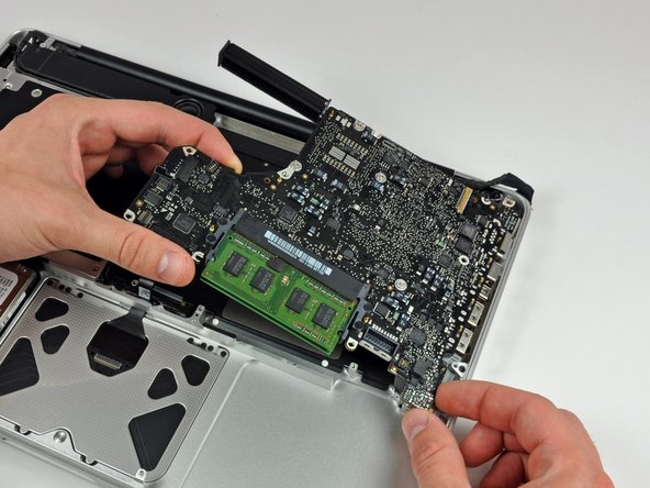 Image 1/2: Pull the logic board away from the side of the upper case and remove it, minding the DC-in board that may get caught.