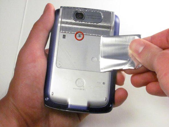 Décoller l'étiquette adhésive sous l'appareil photo à l'arrière pour révéler une vis cachée, encerclée dans l'image vers la gauche.