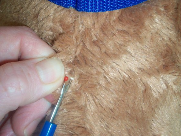 Insert stitch unpicker into seam line and unpick from neck to tail.