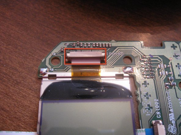 Pull out the circuit board and LCD screen assembly. Pry up on the brown clip to remove the LCD screen.