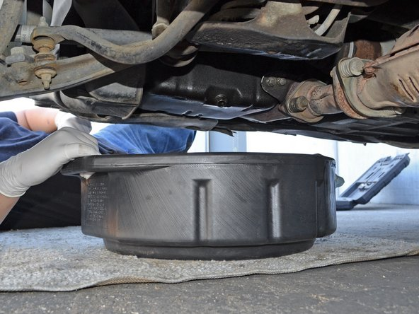 Use a 17 mm socket wrench or box end wrench to turn the oil drain plug counter-clockwise until it is loose enough to turn by hand.
