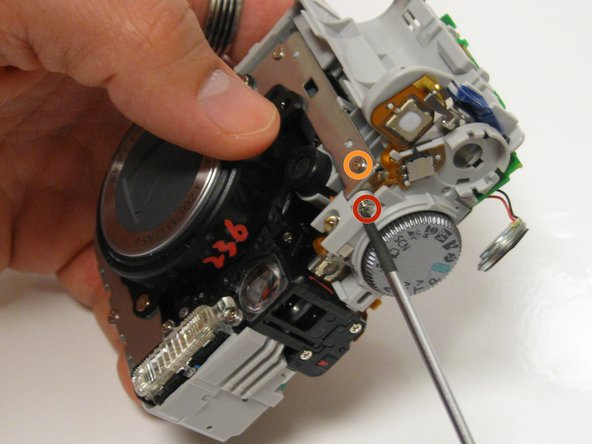 Turn the camera over and unscrew 4.5 mm Phillips head screw that is by the Settings Dial.