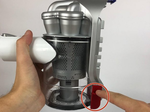 Locate the dust bin's red release lever on the side of the device.
