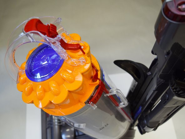 Image 3/3: After pressing down on the red button, the body of the vacuum will easily be removed from the vacuum stand.