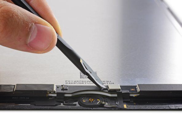 Use the flat end of a spudger to peel up the Home Button ribbon cable and Touch ID control chip.