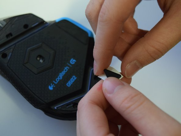 Peel the backing off the new mouse feet to reveal the adhesive.