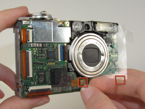 Image 1/1: Lift the clear plastic from the face of the camera, peeling the adhesive just below the zoom lens.