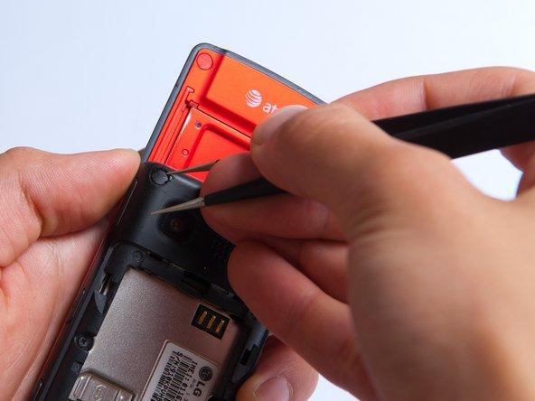 Retirez les deux protections des vis du boitier  en haut du téléphone avec une pince à épiler.