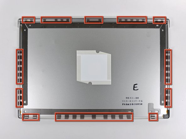 Image 1/1: The picture at left (rear panel already removed) shows the locations of the metal clips (shown in red) that snap on to the front display bezel. In the next few steps, you will use a small flathead screwdriver to release these clips from a ridge around the perimeter of the front display bezel.