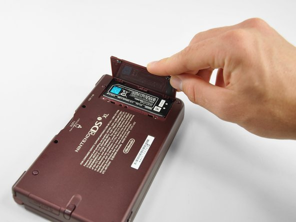 Image 2/2: Lift the battery cover off the back of the DSi XL.