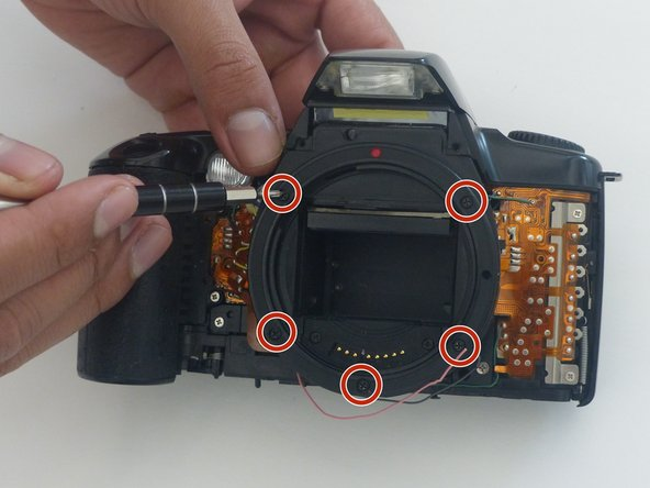 Using a PH000 screwdriver bit, remove the 5 black screws circled in the picture, which are all 5.5 mm in length and 2 mm in diameter.