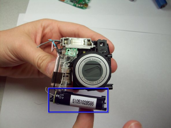 Image 1/2: Locate the capacitor. It is the component that looks similar in size and shape to a AAA battery.