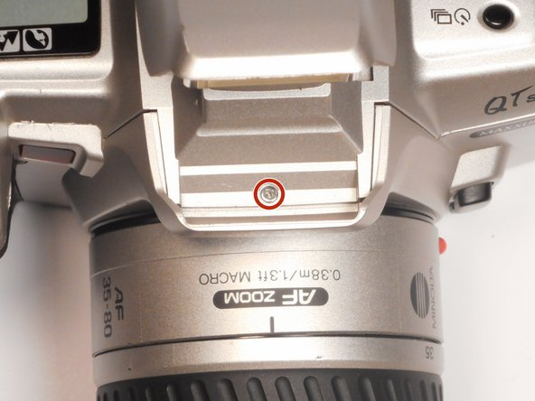 Remove the (1) black Phillips #00 5mm screw from underneath the flash hood.