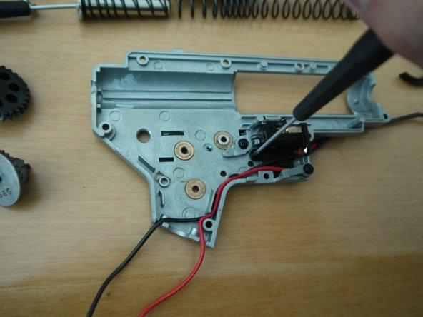 Using a #00 Phillips screwdriver, remove the small screw holding the wire harness in place.