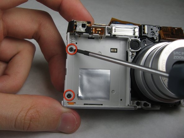 On the front of the camera, in battery case, remove screws indicated: