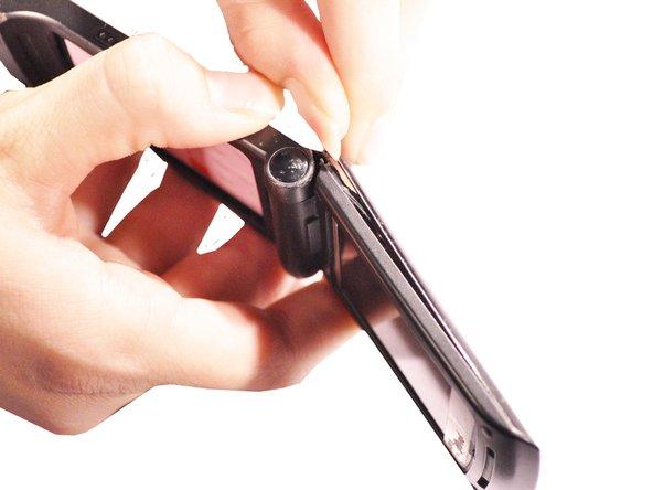 Utilisez un tournevis à tête plate ou des outils d'ouverture en plastique pour vous aider à dégager le capot supérieur du téléphone.
