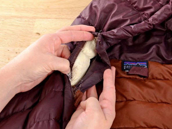 While holding the zipper in place, move the fabric underneath the zipper out of the way so you're only sewing the zipper to one layer of fabric.