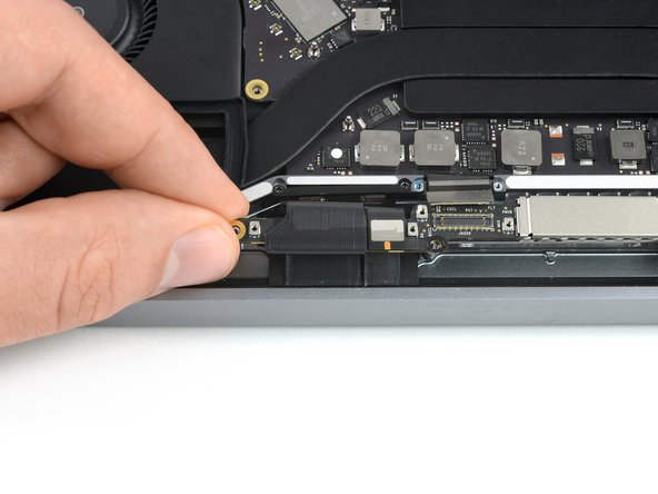 Grab the left side of the display cable assembly and pull it towards the bottom end of the MacBook and away from the  spring hinge.