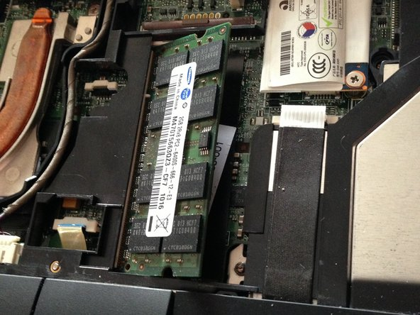 Push metal tabs outwards away from the RAM module to release it.