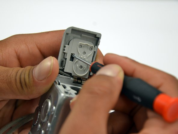 Remove the 4mm Phillips #00 screw on the inside of the flap that hides the battery and memory card slots.