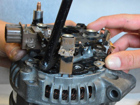 If necessary, use a pry bar to gently raise the top of the bridge assembly off the alternator