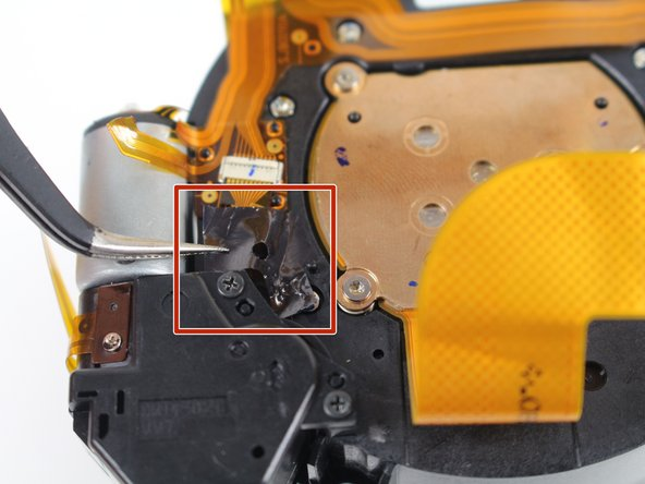 In this step you will remove tape stuck to the top of several electronic ribbons. Be extremely careful when removing the tape, since the ribbons tear very easily.