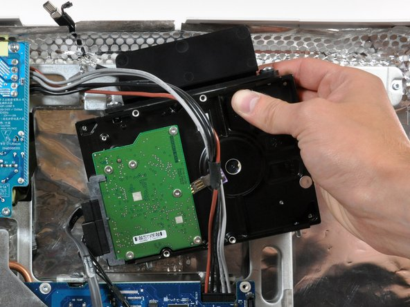 Lift the hard drive (with cables attached) straight up off its lower pins and remove it from the rear case.