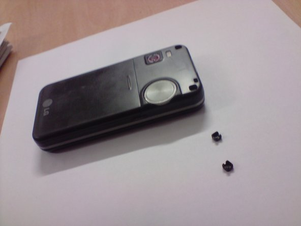 Two plastic clips removed to show the screw heads on the back of the phone.