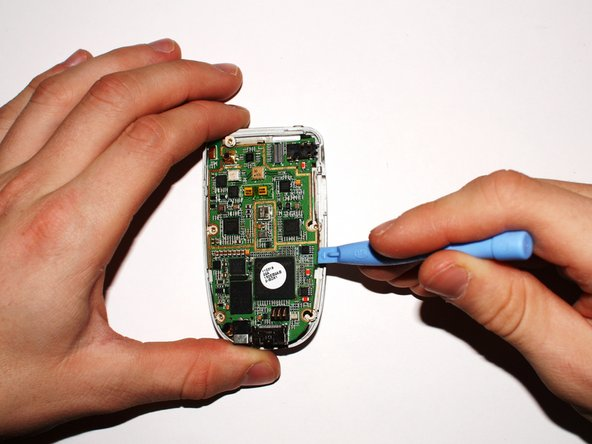 Remove the logic board from the phone by gently lifting up on the large green logic board with the plastic opening tool.