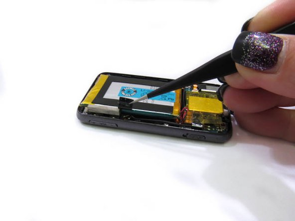Peel back the black tape from the device to the battery from the side of the device.