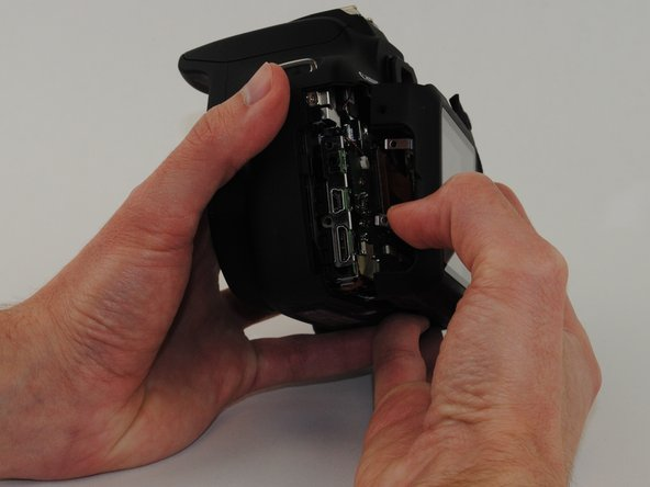 Image 1/3: Gently pry the back panel from the main body of the camera.