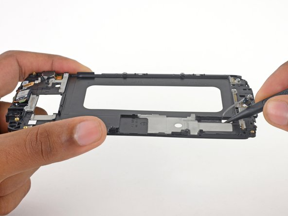 Use the pointed end of a spudger to push the home button cable through the display frame.