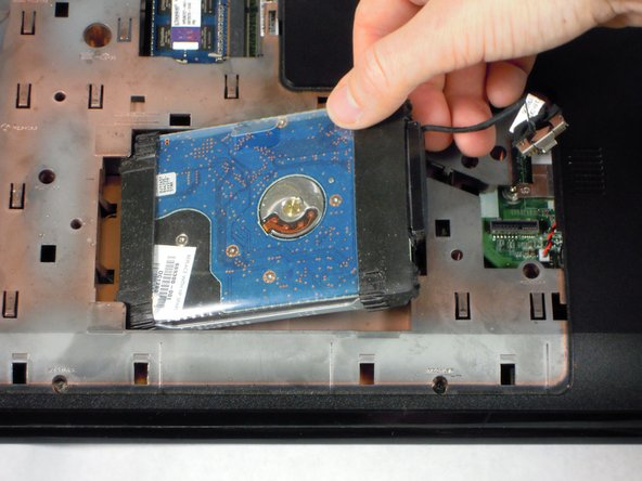 Image 2/2: Pull the hard drive up and to the right to remove it completely from the laptop.