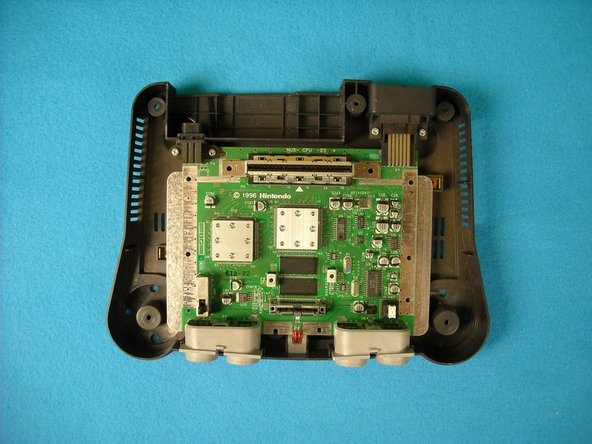 Open the Nintendo 64 in order to operate on the motherboard. Steps to open it can be found here.